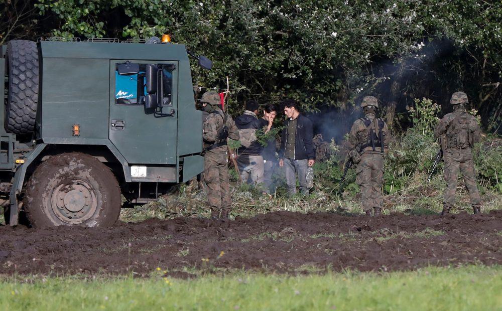 Сотрудники пограничной службы Польши и группа мигрантов на белорусско-польской границе недалеко от города Уснарж-Горны