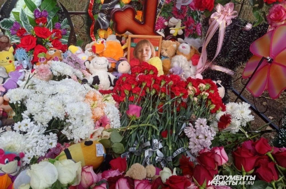 Могила Насти завалена цветами и игрушками.