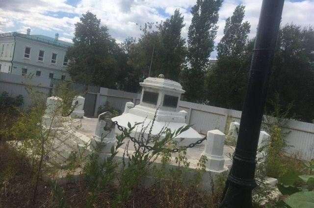 В Оренбурге постамент «маленького Ленина» за забором продолжает разрушаться и зарастать бурьяном.