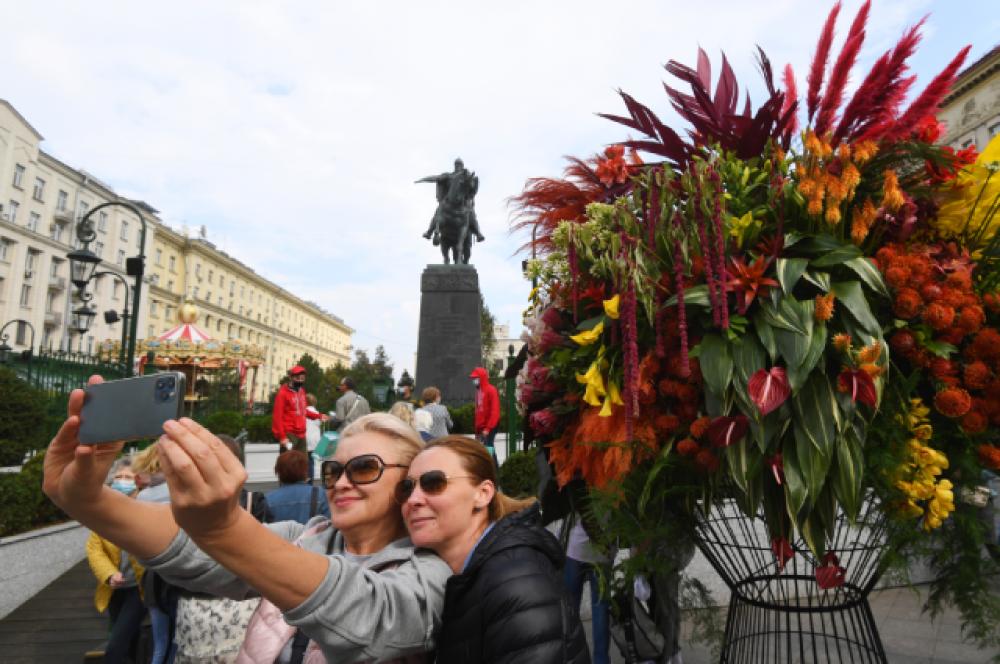 Женщины фотографируются на фоне цветочных арт-объектов на Тверской площади.