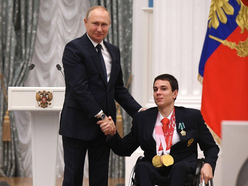 Президент РФ Владимир Путин и трёхкратный чемпион XVI Паралимпийских летних игр по плаванию спорта лиц с поражением опорно-двигательного аппарата в дисциплине 50 м брассом в классе SB3, в дисциплине 150 м комплексное плавание в классе SM4 и в дисциплине 50 м на спине в классе S4, двукратный бронзовый призёр в дисциплине 100 м вольным стилем в классе S4 и в дисциплине 200 м вольный стиль в классе S4 Роман Жданов (справа) на церемонии вручения государственных наград РФ победителям XVI Паралимпийских летних игр 2020 года в Токио