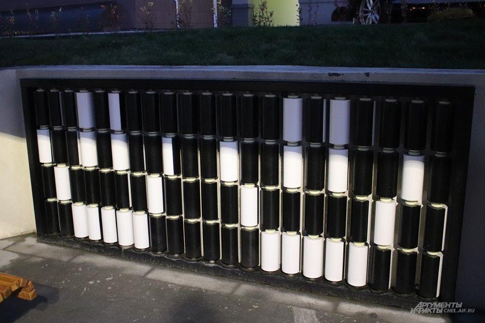 Интерактивная деталь - в стену вмонтированы вращающиеся элементы. Чередуя чёрную и белую стороны этих бочонков, можно оставить послание прохожим.