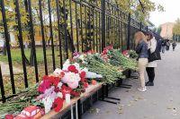 Люди несут цветы к стихийному мемориалу около ограды университета.
