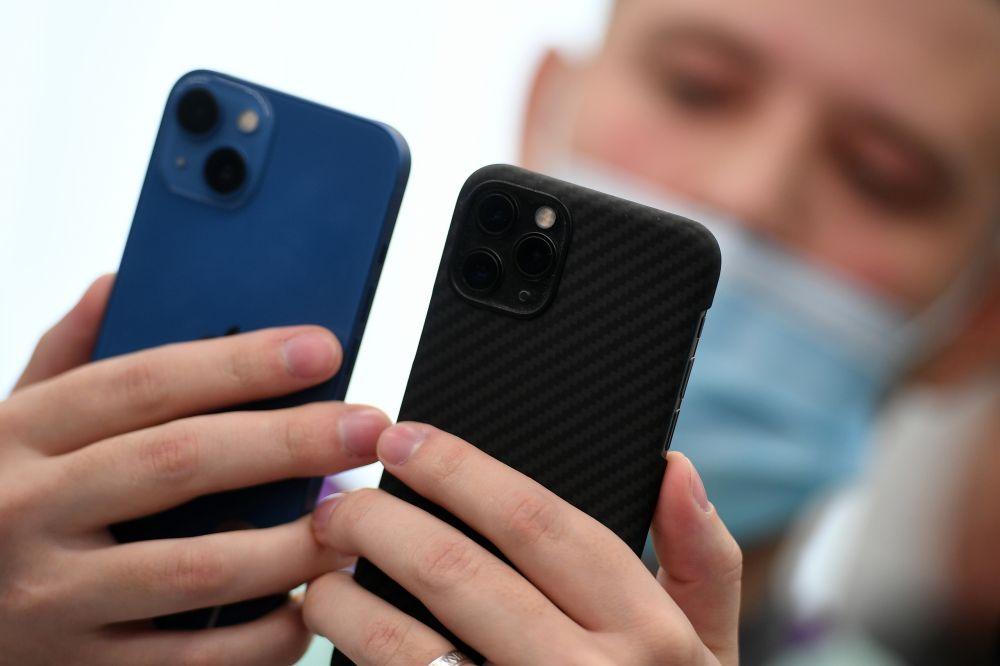 Покупатель держит в руках телефоны компании Apple в магазине re:Store