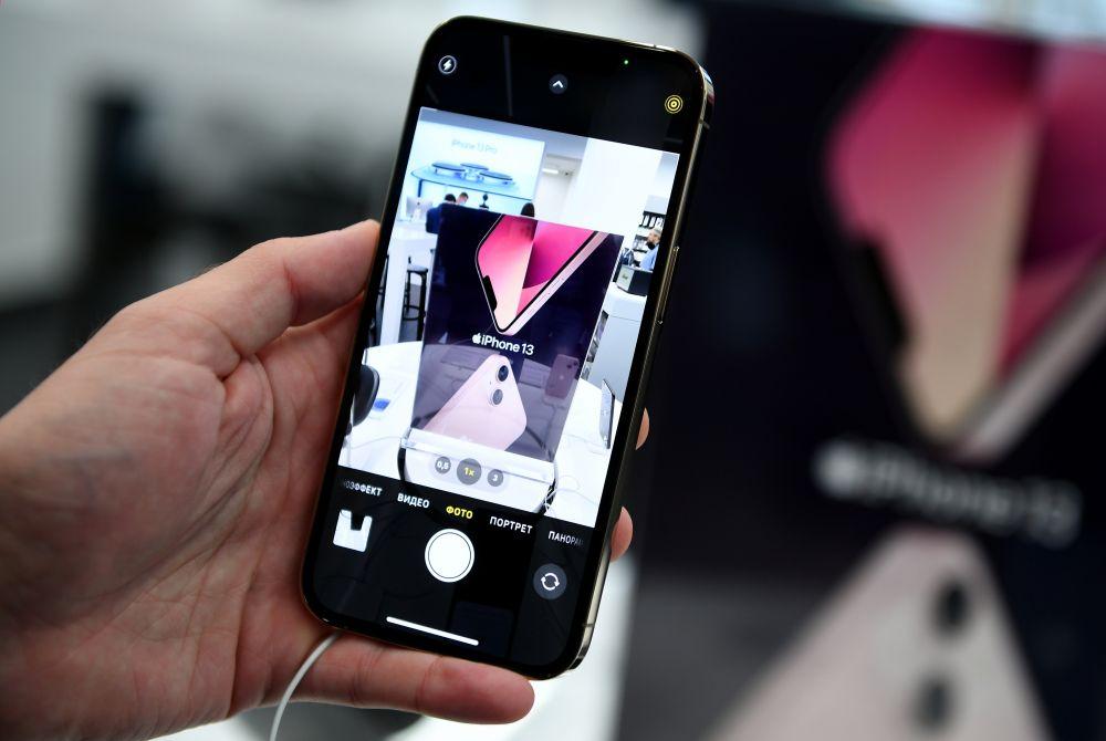 Телефон компании Apple в руке покупателя в магазине re:Store