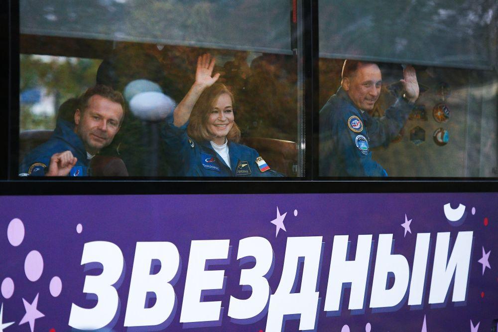 Члены основного экипажа 66-й экспедиции на Международную космическую станцию режиссер Клим Шипенко, актриса Юлия Пересильд и космонавт Антон Шкаплеров прощаются из автобуса с провожающими перед стартом космического корабля