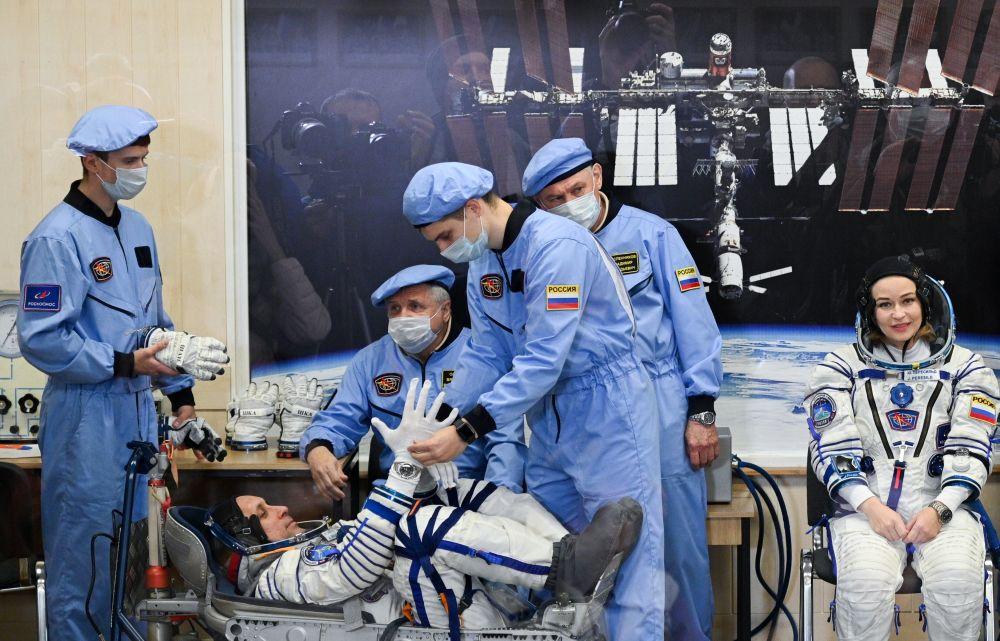 Члены основного экипажа 66-й экспедиции на Международную космическую станцию космонавт Антон Шкаплеров и актриса Юлия Пересильд во время облачения в скафандры перед стартом космического корабля