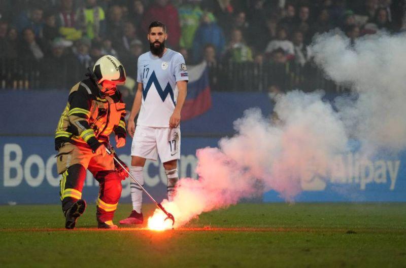 Сотрудник пожарной службы убирает файер, брошенный на поле во время матча отборочного этапа чемпионата мира по футболу 2022 года между сборными командами Словении и России. Справа - Миха Мевля (Словения).