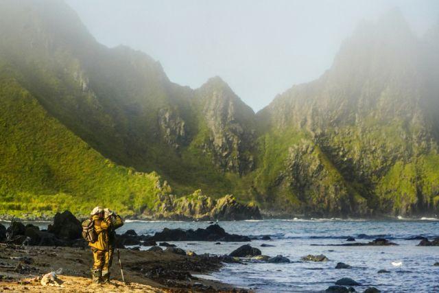 Русский ученый стоит на берегу мыса Васин острова Уруп южной группы Большой гряды Курильских островов.